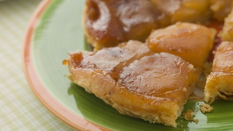 gossipchef:  Apple Tarte Tatin            6 granny smith apples (peeled, cored and quartered) 100 g Butter 150 g caster sugar large pinch ground cinnamon 0.50 tsp vanilla extract or the seeds from a vanilla pod 1 pack of all butter puff pastry whipped cream or vanilla ice cream to serve Method Heat the butter over a medium in a cast iron frying pan (I use a 'Le Creuset' pan about 25cm in diameter). The pan must be suitable for putting in the oven. When the butter foams add the sugar and let it caramelise for a few minutes. Then sprinkle in the cinnamon and vanilla. Arrange the quartered apples cut side up in the pan. Continue to cook for a couple of minutes until the apples soften slightly. Turn off the heat and leave to sit for about 10 minutes. Meanwhile roll out the pastry and use a plate a little larger than you pan to cut out a circle from the pastry. Then carefully lay the pastry over the apples in the pan and tuck it in around the sides. Bake the tart for 25 minutes at 180C. When cooked place a large plate over the pan and turn out your tart. Be very careful as often the juices can escape so normally I do this over the sink with another pair of hands at my disposal! Serve warm with cream or ice cream.