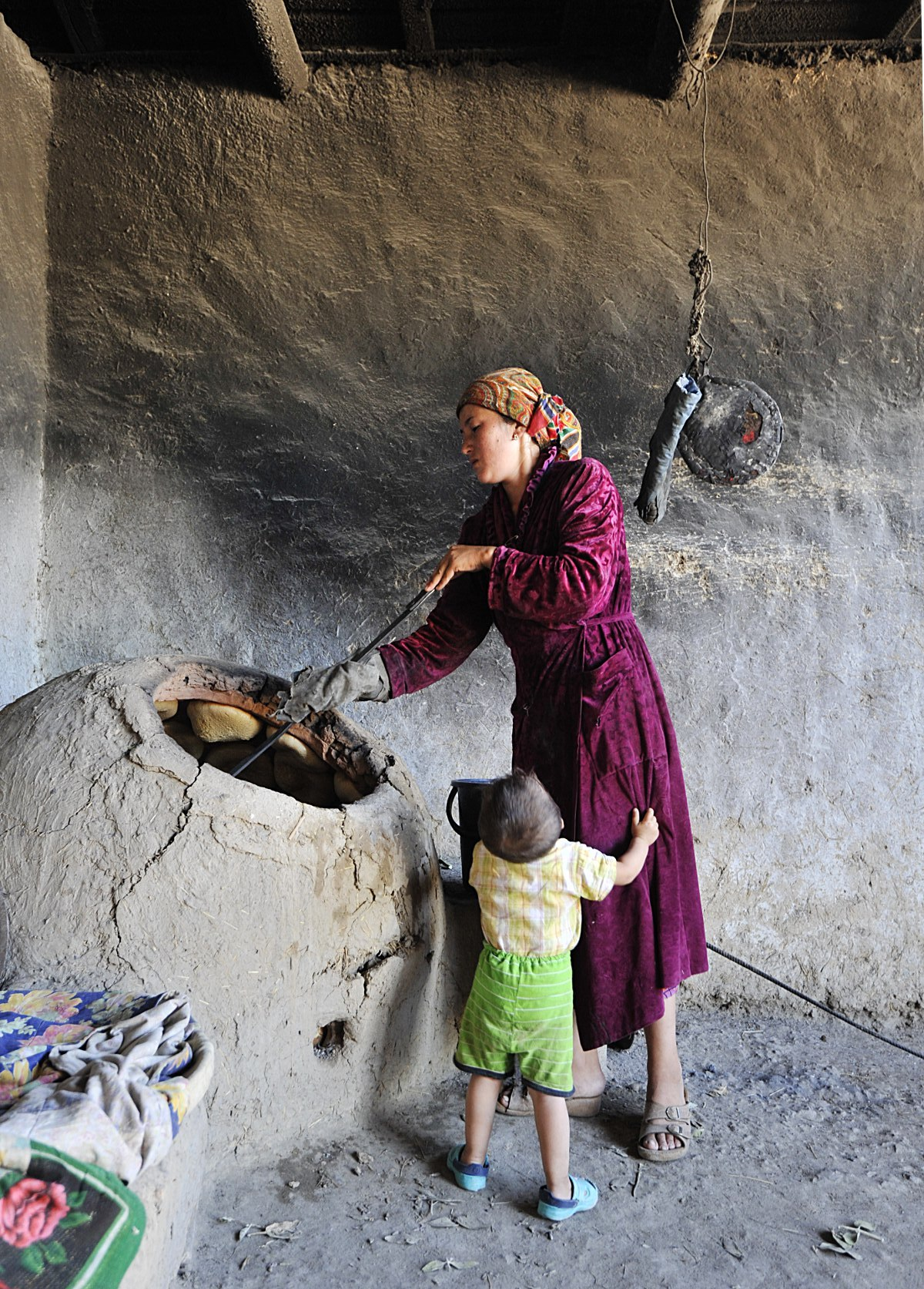 Uzbek Woman Making Naan and Caring for Child, Uzbekistan 2012