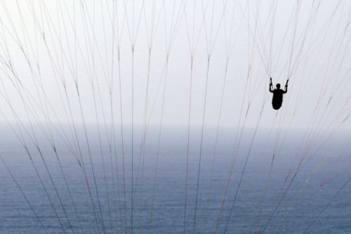timelightbox:  June 6, 2012. A man paraglides behind the lines of another paraglider off the Torrey Pines Gliderport in San Diego. More than 200 years ago, the silhouette was the foremost way to document one's appearance, but it's still widely used in photographic frames today. From capturing the world's protests and politicians to wildfires and war zones, LightBox looks at the use of silhouettes on the wires this month. See more photo here.