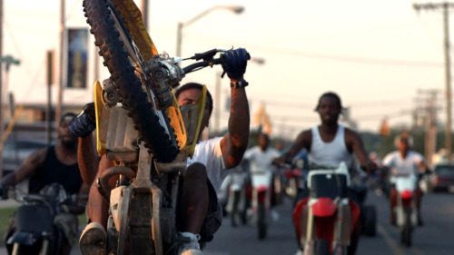 "SWAGGER vicemag:  The Illegal Dirt Bike Gangs of Baltimore There is something undeniably American about biker gangs, from the quintessential images ingrained in our mind of the 60s-era Hell's Angels made legendary by the writing of Hunter S. Thompson and The Rolling Stone's film Gimme Shelter to DMX's video for the ""Ruff Ryders' Anthem"" where he had all those dudes in baggie jeans riding through the ghettos of New York on ATVs and suicycles. It's time to add one more motorist collective to that pantheon of rebels on wheels: Baltimore's Twelve O'Clock Boyz. They're a hundred-strong gang who wheely dirt bikes through a city where police are banned from chasing them, creating an illegal underground sport that the cops are powerless to do anything about. For the last three years, filmmaker Lotfy Nathan has been documenting the Twelve O'Clock Boyz for a new film called Twelve O'Clock in Baltimore (trailer below), which is now ready for release at the end of this year. I spoke to him about the gang.  VICE: Hey Lotfy. How did you first come across these guys?Lotfy Nathan: I saw them first in passing, actually. I think a lot of people in Baltimore see them tearing through the city, and most people don't really know what the whole thing's about. It's assumed that they're pushing drugs on dirt bikes—like a pack of dealers, or bandits, or something—which is kind of ridiculous, because these bikes are incredibly loud and attract a lot of attention, which is not what you want if you're selling drugs.Very true. What made you want to make a film about them?Well, I didn't know if it would actually be possible to contact them at first. But I asked around and found out where they congregated and they were actually really receptive to being filmed. I hadn't really connected the showing-off element of the bike riding to what they might be like in person before, but it kind of made sense. A lot of the guys are going for a YouTube celebrity status, so they were all about the camera. Photo by Noah Rabinowitz I read about the weird situation with the police and the riders. Could you explain that a bit?Basically, the bikes are illegal to ride in the city, but the police aren't allowed to chase anyone riding them, so they leave them alone. It's because of a death that occurred in 1999, involving a dirt bike rider when, allegedly, a police officer was giving chase. It's just too dangerous to chase the bikes. That then creates this awkward cat and mouse thing, because the police are being taunted. CONTINUE"