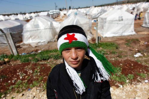 delucazade:  Mohammad (12) a Syrian refugee wearing a scarf with the colors of the Syrian Independence flag, stands outside of Reyhanli refugee camp in Hatay province on the Turkish-Syrian border on March 17. Over the past few weeks, the number of Syrians crossing has increased dramatically with an average of 200 to 300 now coming into Turkey every day. This week 1,000 crossed in just 24 hours, the highest number since the first wave of refugees last summer. Around 15,000 registered Syrian refugees now live in tented camps inside Turkey, making up almost half of the 34,000 people the United Nations estimates to have fled Syria since the start of the conflict a year ago. (Murad Sezer/Reuters)