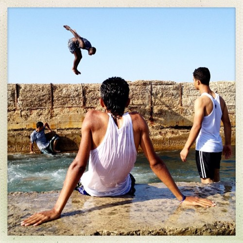 Tripoli, Libya | July 3, 2012 Young Libyans swim on a rubble strewn stone cornish during a hot summer day. #iLibya #magnumfoundatiom #emergency fund #photography #photojournalism #documentary #hipstamatic #libya #tripoli #swimmers (Taken with Instagram)