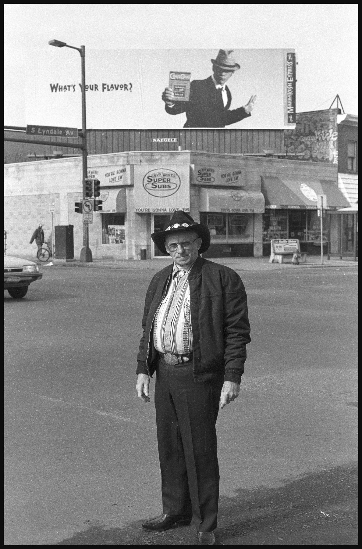 From the Archive - Real Cowboys, Minneapolis, MNLake Street USA (1997 - 2000) [When I met this man he had lost the use of his vocal chords and was using a device that he held to his throat called an electro-larnyx, which amplifies the tissue to create a synthesized, sort of electronic-sounding voice.] Most of 'em here call me cowboy and that's it. There must not be too many around. At least not real ones. I'm from El Paso, but I'm here because I've had two cancer operations at Abbott. When they found the cancer everything happened so fast, I didn't have time to think about it long. By the time I went to the hospital they told me we've got about thirty minutes to cut you open or you're going to be gone. The cancer had wound around my vocal chords. Now I have tubes down there that I breathe through. But I feel lucky. When I get up in the morning and my feet feel the carpet I know I'm still here. I can still communicate. I don't even consider this much of a handicap.  I made most of my living as a heavy equipment operator. But music was my passion, still is, but I can't find one of these things that sings [points to the electro-larnyx]. I sang with Bill Monroe and his Blue Grass Boys out of Nashville, Tennessee. Sang for 35 years. In a month I'm going to Chattanooga. I'm just going back to see if some of those people are still around. I miss singing. It was a big part of my life. I also trained horses when I was young. I still do, even though I'm not supposed to be doing it. I don't know if I would want to live if I couldn't have something to do with horses. Most of my family, my dad and my brother–well they're all dead now–we were all horse people.