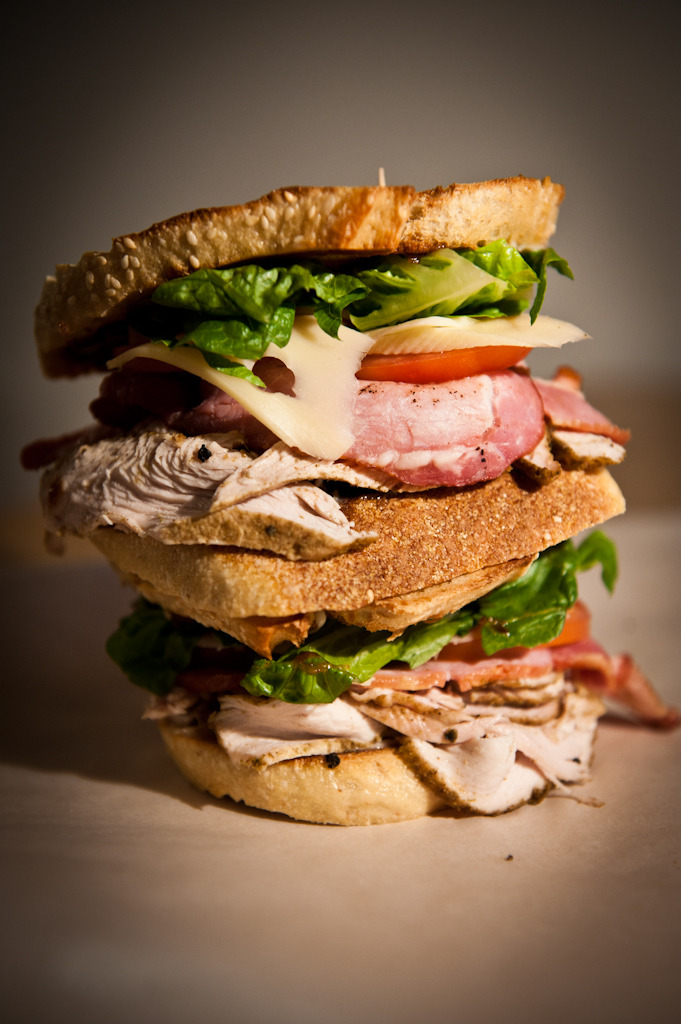 Spiced turkey club with Emmental Experimentation is a good thing - the problem with it is that sometimes, it goes a bit wrong. Frankenstein's monster, Tab Clear, Marmite… everyone knows that there are some things that really should have been left unmade. Sadly, yesterday's sandwich was one of those - a slightly odd concoction involving cod and prosciutto that missed the mark in a manner that you'd expect from a pished darts player.  To make up for it, today's butty is a classic - not an attempt at playing safe, but a determined effort to great a sandwich that will get your saliva glands going, good and proper. Welcome to the Club. Like on a heavy Saturday night in town, when it comes to lunchtime, you can always have a bit of a fun with a club. This tower of power features oven-cooked turkey breast - not chicken - at the core, seasoned with tumeric and sliced wafer thin to keep everything suitably tender. Adding to the Scooby-Doo styling is some thick-cut, smoked back bacon, ripe tomatoes and a few slices of Emmental cheese. As a final flourish, there's some chopped up baby gem (avoiding big chunks of stalk), and a smear of some smoky, sweet jerk hot sauce under the top slice. The Club is one of those butties that makes you smile - it genuinely looks like a cartoon sandwich, rammed with so much flavour and colour that you can't help but feel a little tinge of pride when a colleague scowls at your plate. Bask in it.