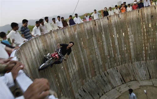 Pakistanis enjoy thrill ride Mohammed Iqbal, 41, rides his motorcycle around a circular vertical track in an entertainment park in Islamabad, Pakistan on July 3, 2012. Read the complete story.