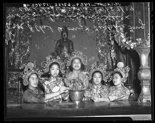 Girls in costume sit in front of Budda during Autumn Moon Festival in Los Angeles' Chinatown, 1939