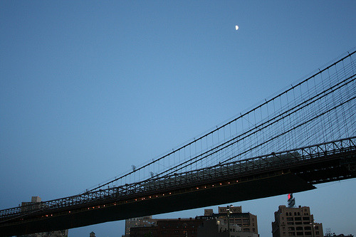 Moon over the Brooklyn Bridge at dusk.