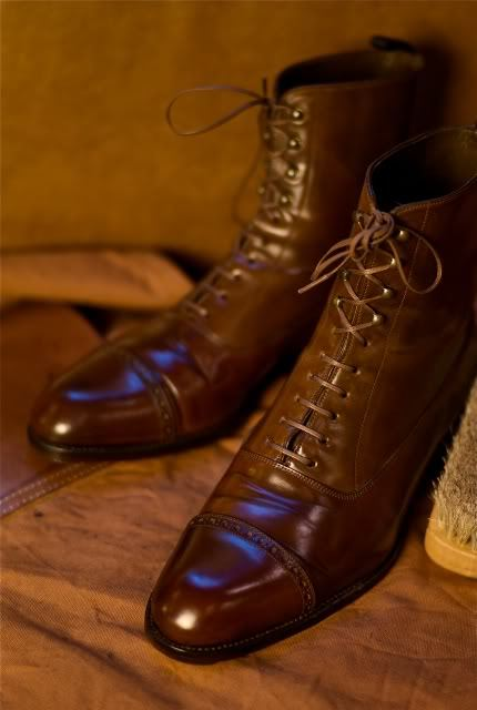 "Shell Cordovan for Foul Weather Boots Pictured above is a beautiful pair of cognac shell cordovan boots, custom made by Carmina for Ethan Desu. As Ethan notes, these are his go-to wet weather boots, and they've taken quite a beating in their time.  Shell cordovan is also my material of choice for rainy day footwear. Some men worry that harsh elements will ruin their ""precious"" shell cordovans, but it's important to remember that one of the material's main advantages is its toughness. You can walk through hail, rain, sleet, or snow in these things and your feet will stay bone dry. Yes, this may cause the leather to rise a bit in some places, but you can smoothen it out by rubbing it with a deer bone (or simply the curved side of a metal spoon), and giving it a vigorous brushing. If you wish, you can also help protect the leather by applying a bit of wax polish once or twice a year (any more and shell cordovan won't shine up well).  Just take a look at the gleaming pair of shoes above. Although Ethan uses these as his rain boots, and has put in a lot of wear, he's taken a stiff brush and a little bit of water, and made them look better than most people's pampered dress shoes.  Don't be afraid to use your things."