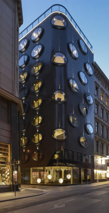 arcilook:  Extraordinary Bubble Facade of Hotel Topazz by BWM Architekten und Partner BWM Architekten und Partner have designed this unique facade of the Hotel Topazz in Vienna, Austria. The facade absorbs and reflects the natural light, ensures that this building – on one of Vienna's smallest building sites – is a real eye-catcher. The design is characterized by striking elliptical window openings that jut out slightly. This unconventional, distinctive treatment of the facade gives this round-cornered building a sense of weightlessness and elegance as well as an unusually physical presence within the fabric of Vienna's historical architecture.