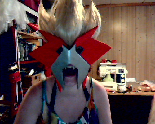 The Entei mask is done, seen here with part of the wig and my Fabulous Fangs. okay fine it's done i need to paint the eyeholes and probably add black tulle on the backside you can't really see it in the picture because of low quality cam, but the mask has angles and shit. cosplayers love angles and shit. it stays put thanks to an elastic band that goes around my head and attaches to the mask with hooks. the wig goes over the band.