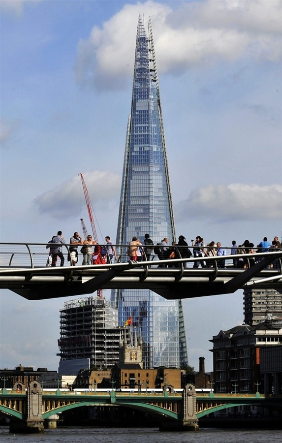"Europe's new tallest building: An 'iceberg' in heart of London or titanic $2.35B folly? LONDON — Built at a cost of $2.35 billion in tough economic times, Europe's new tallest skyscraper has become a lightning rod for criticism even before it officially opens Thursday. Rising more than 1,000 feet above London's skyline with floor space equivalent to 31.4 acres — or close to 15 football fields —  the Shard is Europe's boldest and most extravagant building. It was funded by Qatar's royal family, who boast pockets as deep as the tower is high. But it's more than just sheer size that gives the tower its swagger. The building's design is already iconic. It's crafted from 11,000 glass panels, which resemble shards of glass (hence, its name). They incline inwards as they rise to the top culminating in a sharp-angled jagged spire. The shards never touch and there are fissures along the way, which allow the entire structure to ""breathe.""   Read the complete story."