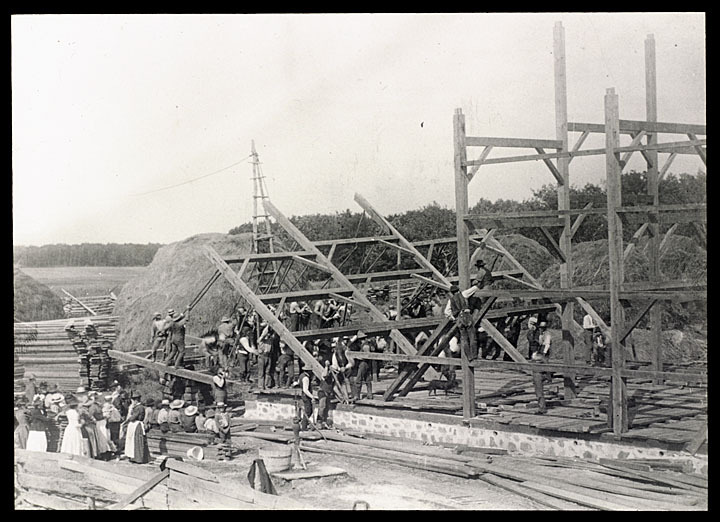 Barn raising on Alva Paddock farm, Kenosha County, Wisconsin, 1891. Photographer Louis Milton Thiers captured a local barn raising in action as a group of men lift a frame into place. via: Kenosha History Center by way of University of Wisconsin Digital Collections