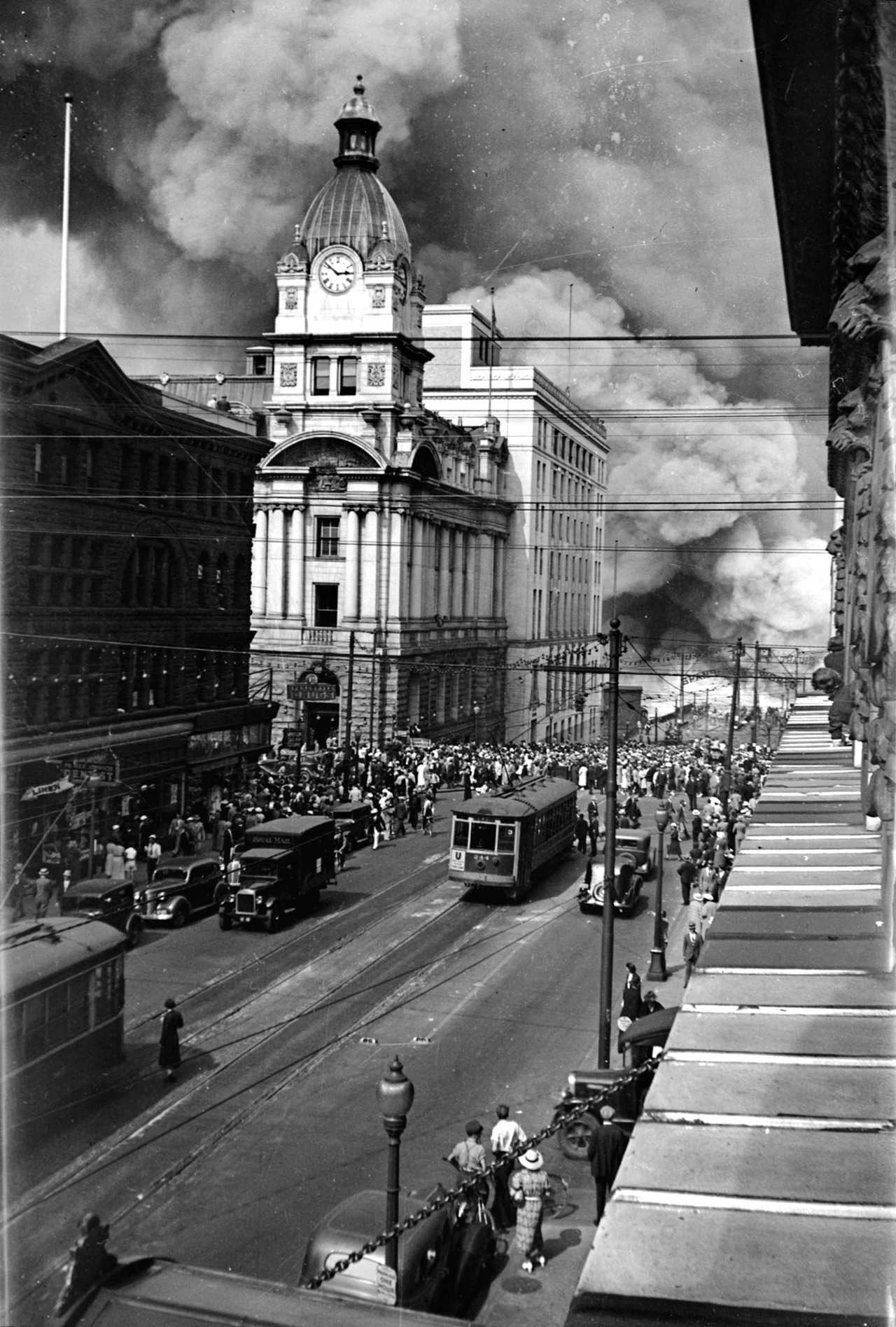 "Granville Street looking north, Wednesday 27 July 1938 Smoke from a massive fire at the CPR's Pier ""D"" at the foot of Granville Street. The fire caused about $2 million (in 1938 dollars) damage. Chuck Davis provides a blow-by-blow account from VFD historian Alex Matches here.  Source: City of Vancouver Archives #Can N34"