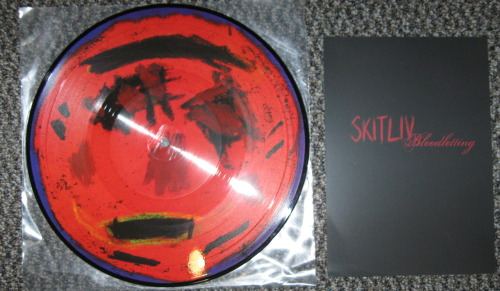 "Skitliv - ""Bloodletting"" (Cold Spring Records 2010) I don't get why this record is just advertised as Skitliv; it has both Skitliv on it and Current 93.  If anything it's a split between the two bands.  Whatever, I'm just trying to be consistant to the rest of the world that says this is just Skitliv [EDIT: the Cold Spring website says the first track is an intro by David Tibet of Current 93; still stupid because it's listed as Current 93 in the linear notes. Whatever].   Skitliv is a doom metal band fronted by original Mayhem vocalist Maniac.  I don't know what I was expecting from this band when I first heard them, because I always though Maniac was a little lame (as a person, not musically), but fuck this record is great.  It's not just doom metal, there is a lot of elements from noise and industrial music peppered all over this picture disc.  The first Skitliv track has sheets of noise skree crashing in and out between the riffs.  Kind of like the Porn + Merzbow collaboration record with Maniacs sick vocals.  The second side is a slow burning jam, more like a funeral dirge than a doom metal track but is the abrasive funeral dirge ever.   Cool little record, even if it is a picture disc.   -Log."