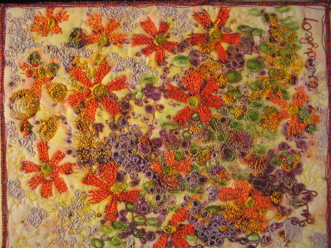 July by Threadborne The little orange flowers with purple buds are free machine embroidered  on a background of melted wax crayons.