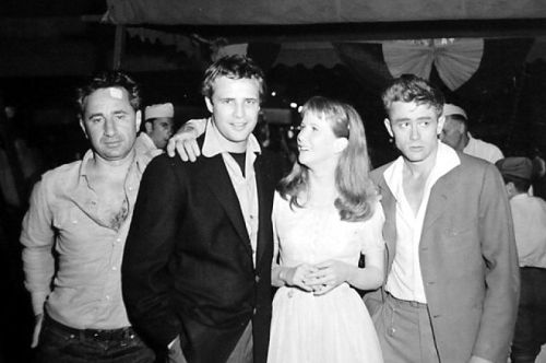Director Elia Kazan, visitor Marlon Brando, Julie Harris and James Dean pose on the set of East of Eden