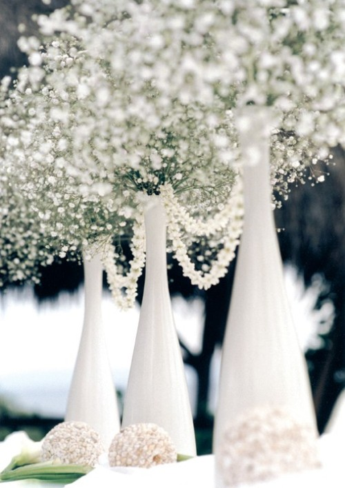 my-big-fat-wedding-kitsch:  Recycled wine bottles and baby's breath—cheap simple centerpieces.