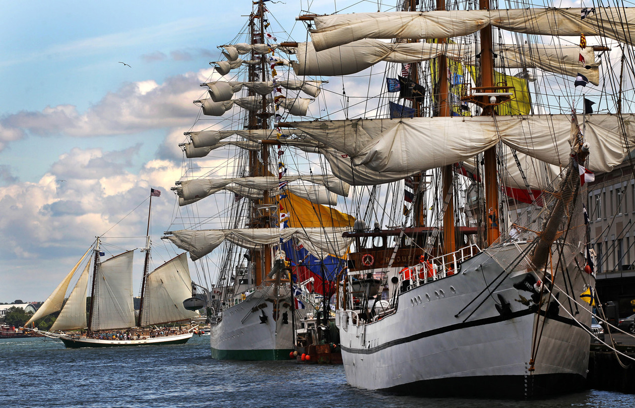 The Tall Ships depart from Boston Harbor. (Globe staff photo / David L. Ryan) » More photos How photographer David L. Ryan captured the shot: At Fish Pier, I noticed how the view with clouds and ships appeared with the sunlight behind me. The sun was covered on and off with the clouds. With 100mm-400mm lens I waited and was lucky to see another sailing ship pass along with a bird in the sky. The sun peeked out and I clicked off some frames. It does pay to wait and take more shots than you think.