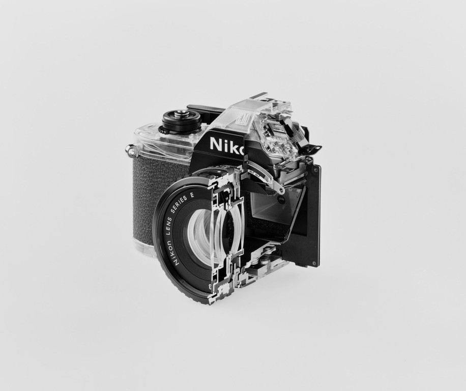 "Christopher Williams / Cutaway model Nikon Em. Shutter: Electronically governed Seiko metal blade shutter, vertical travel with speeds from 1/1000 to 1 second, with a manual speed of 1/90th. Meter: Center-weighted Silicon Photo Diode, ASA 25-1600, EV 2-18 [with ASA film and 1.8 lens]. Aperture Priority automatic exposure. Lens Mount: Nikon F mount, Al coupling [and later] only. Flash: Synchronization at 1/90 via hot shoe. Flash automation with Nikon SB-E or SB-10 flash units. Focusing: K type focusing screen, not user interchangeable, with 3mm diagonal split image rangefinder. Batteries: Two PX-76 or equivalent. Dimensions: 5.3"" x 3.38"" x 2.13"" [135mm x 86mm x 54mm], 16.2 oz [460g]. Fotostudio Axel Gnad, Düsseldorf October 17, 2008 [b&w]"