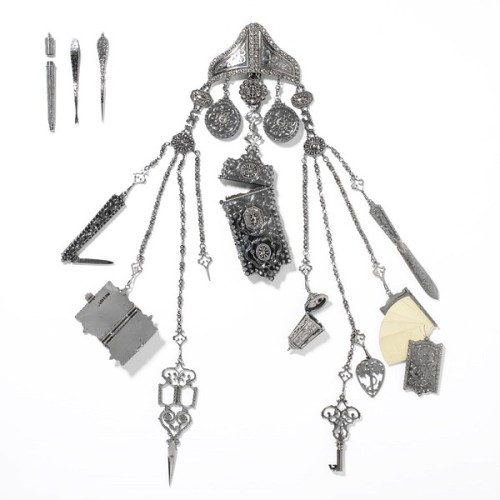vicfangirlguide:  A chatelaine which was displayed at the Great Exhibition of 1851. Before the 1850s pockets were uncommon in female clothing and so women used chatelaines as a fashionable, decorative means of carrying small and useful items. The chatelaine would be hung from a belt and, through a series of clips and chains, contain a variety of objects such as scissors, keys, scent bottles, penknives, tweezers, writing pads and letter openers.