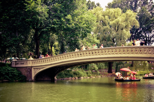 "Red umbrellas and row boats under Bow Bridge. Summer. Central Park, New York City  Sometimes there are moments that are so beautiful that they leave imprints on your heart forever.  —-  View this photo larger and on black on my Google Plus page  —-  Buy ""Saturday Afternoon in Central Park - New York City"" Prints here, email me, or ask for help."