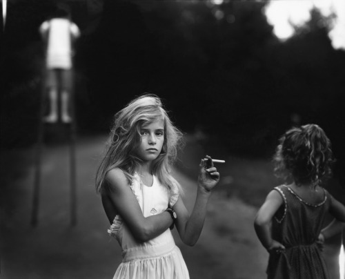 tristetriste:  Candy Cigarette, 1969 by Sally Mann  Sally Mann's famed body of work Immediate Family documents her three children, Emmett, Jessie and Virginia, in an array of scenes at their home in the foothills of the Blue Ridge Mountains in Virginia. Capturing them as they sleep, interact, dress up and role play. Mrs. Mann's photographs highlight a heightened maturity that defies their age, creating a tension between the push of childhood and the pull of adulthood. Even when the scenes themselves are innocent, there is a knowing gaze from the subject that, in my opinion, charges the image itself. In Candy Cigarette (1989), Mrs. Mann's eldest daughter Jessie stares defiantly at the camera, at her mother, with tousled hair and a cigarette made of bubblegum. Something which I personally find rather fascinating in that photograph is that Jessie is exhibiting a self-awareness as both a female and also as a subject of her mother's lens. While Mrs. Mann's work has consistently come under public scrutiny for its intimate subject matter, at the root of her project, Immediate Family is a family album filled with the stories, memories and moments that define Sally Mann as a mother and as a photographer.