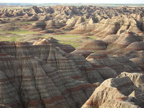 Strata is a term we use in geology and stratigraphy, which is the rock layers/bands clearly defined like in the photo above. The word stratum is for one layer, whereas strata is for multiple layers. The photo above is by calwest on Flickr, which is a photograph of the Badlands in South Dakota.