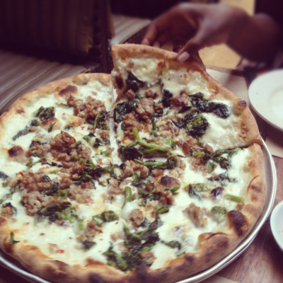 Two single girls going halfsies on a broccoli rabe & sausage pizza at Emporio, each accompanied with a glass of chilled rose.