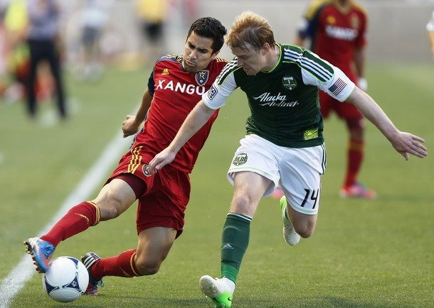 SANDY, UT - JULY 7: Tony Beltran #2 of Real Salt Lake takes the ball past Steven Smith #14 of thePortland Timbers in the second half of an MLS soccer game July 7, 2012 at Rio Tinto Stadium in Sandy,Utah. Real Salt Lake beat the Portland Timbers 3-0.
