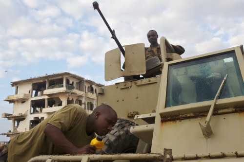 Ugandan soldiers performing daily maintenance to a South African Buffel APC