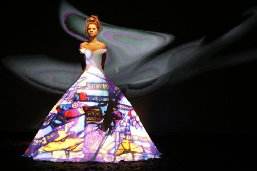 "Fashion 2.0: 14 Dresses in a Single Ballgown For the launch of his Fall/Winter 2012-2013 collections on July 4 in Paris, designer Franck Sorbier saved a nightmarish amount of fabric and thread by going almost fully digital: sharing 14 new dresses with the world by projecting each creation onto one enormous flowing white ball gown. Two models were used as his designs unfolded in the form of a fairy tale. One played the princess and one played the sorceress. The sorceress (at right) used a laptop to cycle through the collection projected onto the gown while recounting Donkeyskin, the tale of a king determined to marry his daughter to fulfill his wife's dying wishes. The daughter, hoping to avoid this destiny, finds a fairy godmother who tells her to make impossible dowry demands, like a dress the colour of the sky and a frock as bright as the sun. ""It's about how with a little imagination you can bring together two worlds that are diametrically opposed,"" said Sorbier, ""and it is about how we can take haute couture into the future to ensure it survives.""  There are worse bedmates than tech and high fashion. Remember when Johanna Blakley said non-copyrighted industries — including fashion — tend to innovate and compete more readily than copyright-protected ones? It's right up there with cars and food. To be fair, Jeremy Danté points out the show bears a reasonable resemblance to Viktor & Rolf's Blue Screen Collection in 2002 — another really cool concept where small elements of couture hosted luminous and ever-changing projections. But if this is the future, we don't ever want to go back. Not if it means the stress of staring into the cavernous depths of The Closet could be wiped away forever, relegated to quaint past as our chic white space jumpsuits change colour swatches for us. See the full gallery of images at Hello Magazine."