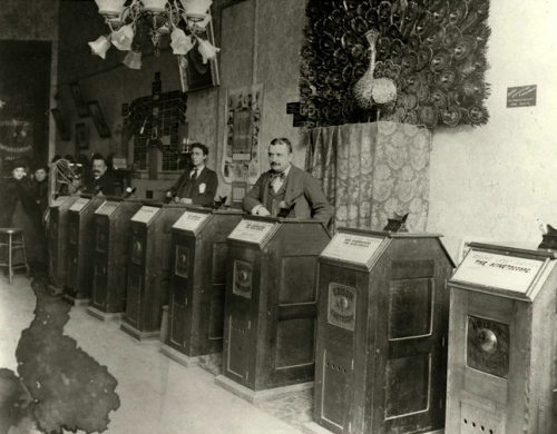 kateoplis:  A Kinetoscope parlor in San Francisco, circa 1895.  GO back far enough in the history of the Big Screen, back to the 1890s, and you'll find no screen at all. The earliest motion-picture viewing was a solitary experience. One looked through a peephole at the top of a Kinetoscope, a waist-high cabinet in which a light illuminated the frames of a continuous film loop. A magnifying lens was attached to the peephole, but the images remained tiny. That means the first cinematographers didn't have much to work with. When projection arrived, movie images could be made life-size in a theater, then larger than life, on a big screen accompanied by big sound. Taking in a movie became not just an immersive experience, but also a social one, with members of the audience sitting in the dark together, laughing, crying and shrieking. Today, we've reached the acme of technical sophistication — and have come nearly full circle. Movie watching is, again, a solitary experience, involving small images on a laptop, a tablet and, tinier still, a cellphone.  Yes, Norma Desmond, the pictures are getting small again | NYT
