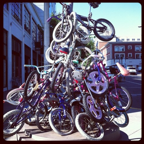 "This bike sculpture photo, taken in Portland, Oregon, by Tess Vigeland, intrigued me when I spotted it on Instagram last week. Do any of you know the back story behind this assemblage of bicycles? If so, tell us. I, for one, am curious. My quick ""Portland bike sculpture"" Googling didn't turn up anything that looks like it's related to this. Don't some of the bike wheels look like they might be in pretty good shape?  (photo used with permission: tessvigeland • Instagram)"