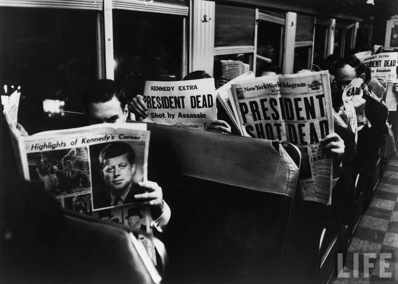 Commuters reading of John F. Kennedy's assassination. New York, 1963. By Carl Mydans