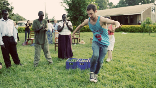 Chris Scott performing for a group of traditional dancers at a secondary school in Gulu.