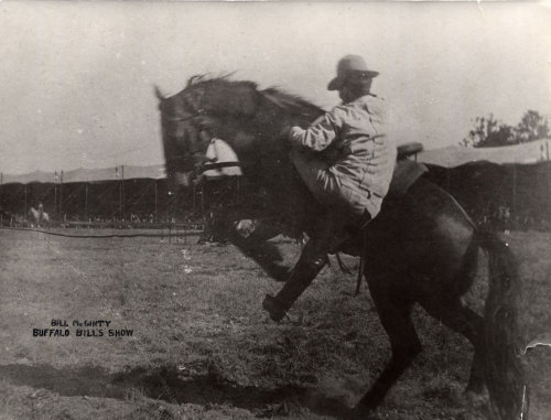 William McGinty mounting a bucking horse inside the arena of Buffalo Bill's Wild West and Congress of Rough Riders. Probably taken during a performance.