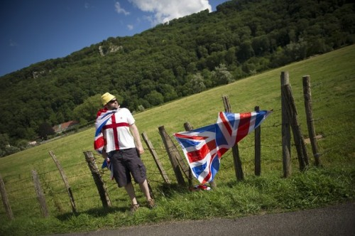 A fan stands on the roadside with British flags as he wait for riders during the 41,5 km individual time-trial and ninth stage of the 2012 Tour de France cycling race starting in Arc-et-Senans and finishing in Besancon, eastern France, on July 9, 2012. (via Photo from Getty Images)