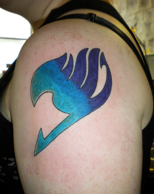 My Fairy Tail guild tattoo, colours based on my favourite character, Erza Scarlet's guild mark which is blue and my own favourite colour, dark purple. Placed on my left arm, like Erza's, but higher up so that it's easier to cover up at work. I'm an official member of the guild, now all I need is the magic powers! Inked by Joe at Joker Tattoo Studio in Belfast, Northern Ireland.