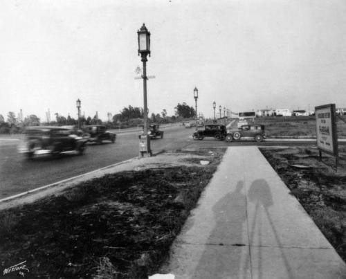 Early morning on Wilshire Blvd near Odgen Ave in 1931.   Looking west. Note the oil derricks in the background of the top left.