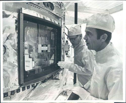 """Astronaut Alan B. Shepard, right, and Kenneth P. Timmons, Martin Marietta Aerospace executive, inspect the Skylab orbiting laboratory's optical window at the Corporation's Denver division. The window was meticulously hand-polished for weeks to attain an optical quality that will allow any cameras to scan the earth as if no window were present. It is located in the Skylab Multiple Docking Adapter which was assembled for NASA's Marshall Space Flight Center, Huntsville, Ala. The docking adapter will serve as an experiment control center and space dock for arriving Skylab crewmen when the orbiting laboratory is put to use in 1973."""