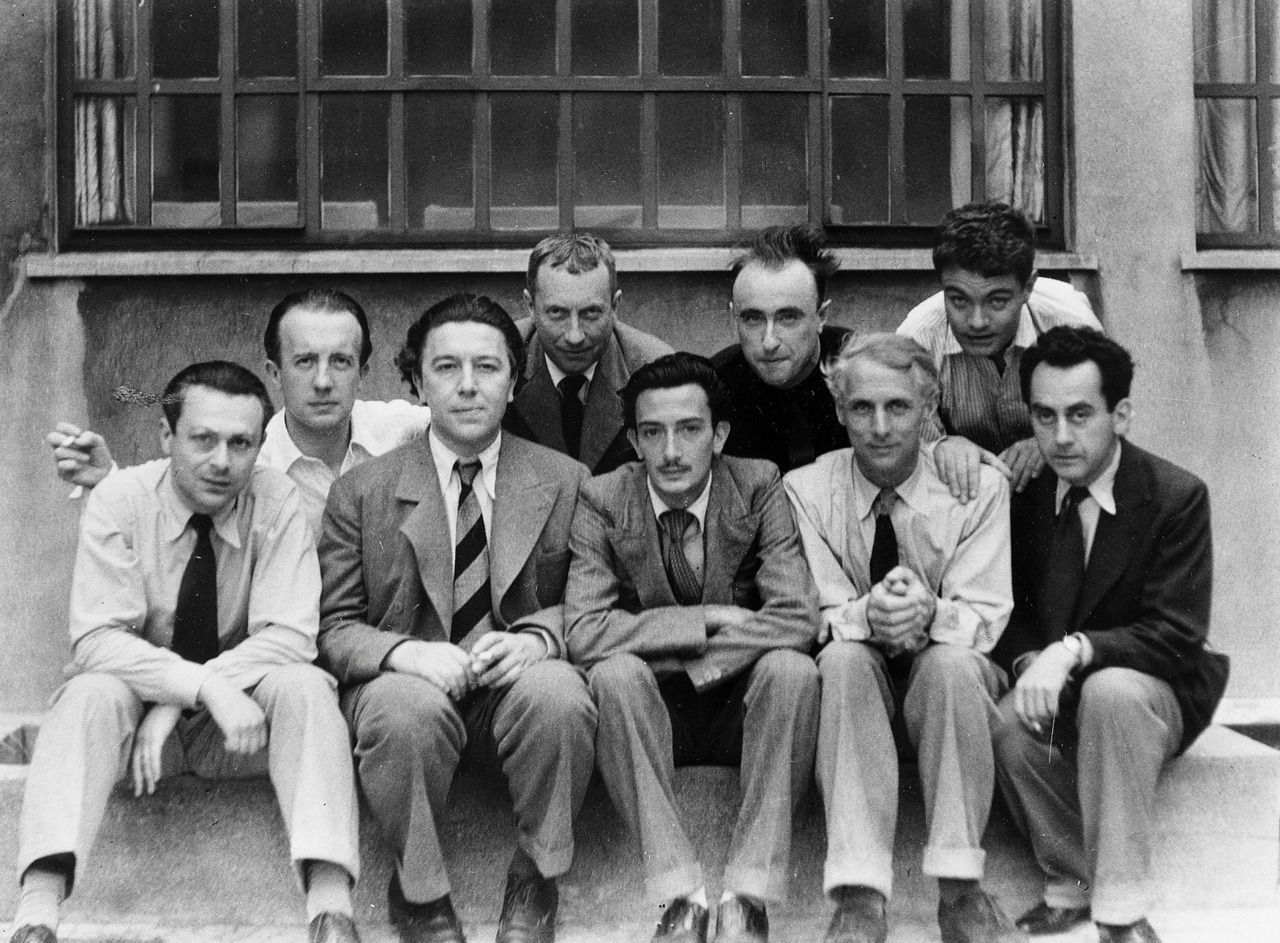 The Paris surrealists, 1933: Tristan Tzara, Paul Éluard, André Breton, Hans Arp, Salvador Dalí, Yves Tanguy, Max Ernst, René Crevel and Man Ray. Photo by Anna Riwkin-Brick (Riwick took several photographs of the group)