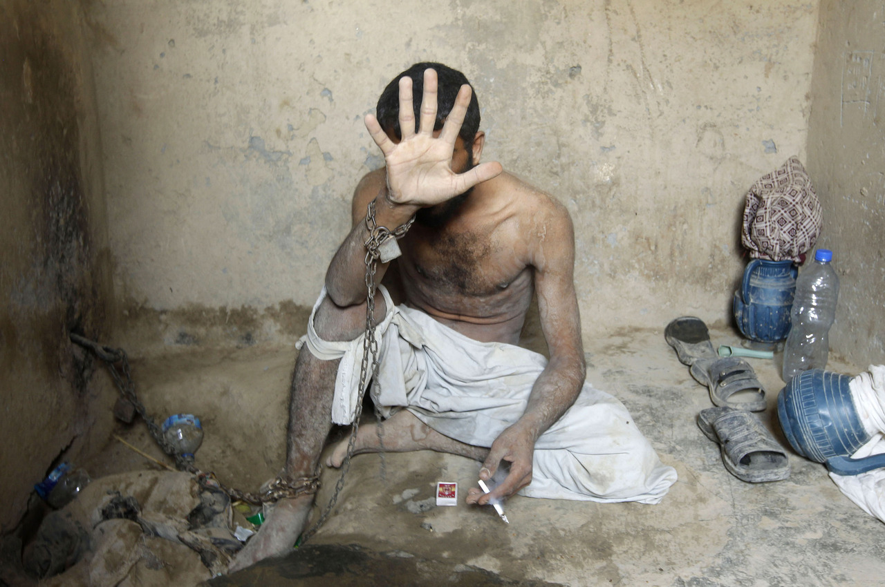An Afghan man with mental health problems shields his face from the camera as he is chained to a wall of a room at the Mia Ali Baba shrine, in line with a traditional belief that spending 40 days chained in isolation at the shrine can cure the illness, in Jalalabad July 9, 2012.  Afghanistan is struggling to fight the mental health problems that afflict some of the population after decades of violence, according to Abdul Rasool, an official from the health department of Jalalabad province. REUTERS/Parwiz