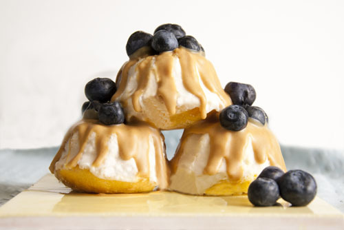 Peanut Butter Blueberry Bundts Mini bundt cakes with vanilla lemon icing, Smooth Operator peanut butter drizzles, and blueberries. Conceived By Lee ZalbenPhotography By Andrea Hernandez