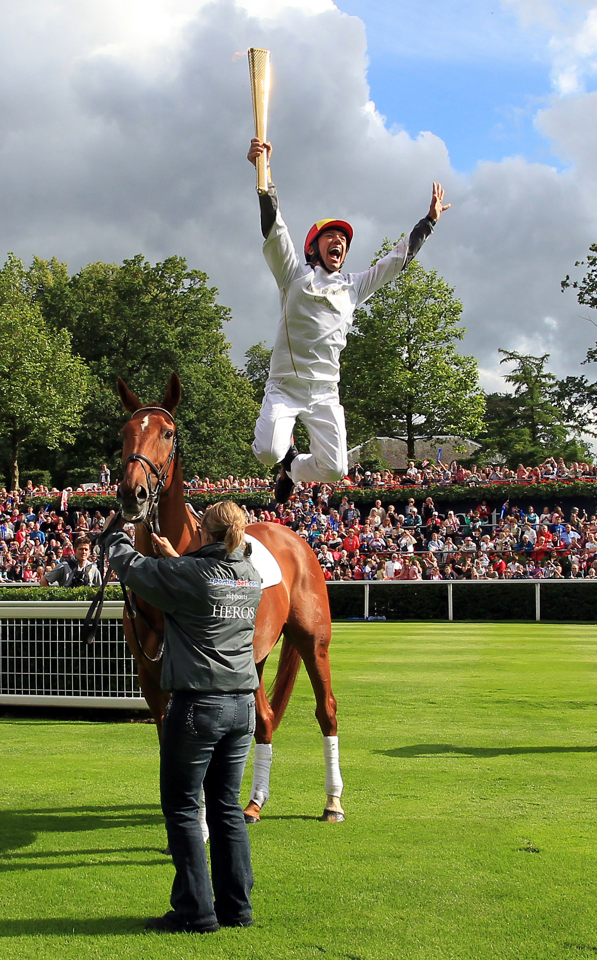 Let the Games begin…soon: Jockey Frankie Dettori leaps from ex-racehorse Monsignor after they carried the Olympic Flame around the parade ring at Ascot Racecourse during day 53 of the London 2012 Olympic Torch Relay on July 10, 2012 in Windsor, England. The Olympic Flame is now on day 53 of a 70-day relay involving 8,000 torchbearers covering 8,000 miles.Photo: LOCOG via Getty Images