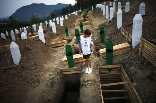 thereligionofpeace:  A Bosnian Muslim boy searches new open graves for the coffin of his relative, which was prepared for a mass burial at the Memorial Center in Potocari, near Srebrenica July 10, 2012. The bodies of 520 recently identified victims of the Srebrenica massacre will be buried on July 11, the anniversary of the massacre when Bosnian Serb forces commanded by Ratko Mladic slaughtered 8,000 Muslim men and boys and buried them in mass graves, in Europe's worst genocide since World War Two. (Reuters)