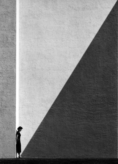 "seensense:  Approaching Shadow, Hong Kong, 1956/2012, Fan Ho. From Hong Kong Yesterday.  I find that popular old photographs depicting Hong Kong, and probably Asia, tend to be drenched in orientalism (see orientalism in art history and Edward Said's writings). They are valuable historical accounts, but angled through Western eyes: this is a sampan, this is a fish market. No doubt fascinating glimpses into the past, but rarely is there any room for contemplation. And then there is Fan Ho. His approach is subtlety and abstraction, new perspectives and technical perfection. Much like László Moholy-Nagy and Albert Renger-Patzsch, prominent figures in the school of Bauhaus, Fan Ho's subject matter is never about the big picture. In his work are the mundane, every day objects, and life. He prefers the minute and often unnoticed moment of intimacy (see Little Women and Back to Mother here), over what outsiders may perceive as very Hong Kong. He prefers playing with shadows and architecture, over matter-of-fact captures of the street. Photographs of old Hong Kong are typically shot in a documentarian manner (see geewhizgolly's old Hong Kong tag), but Fan Ho shoots like a painter. The war brought about social and political fragmentation everywhere. A pictorialist takes a sentimental approach bordering on propaganda: this is a poor starving child, this is a bloodied soldier. The photographer presses the shutter to express his political ideologies. But those sick of political strife, created new objectivity where every message is stripped off, and where art and photographs show nothing but its intrinsic aesthetic value. But here comes the plot twist, the results are rarely just emotionless objects, they do trigger our own memory and give us room to contemplate the people in the picture. They say nothing, but it doesn't mean there is nothing to say. You don't look at Fan Ho's photos and gasp at how political, how oriental they are. You just say, ""Shit, this is beautiful."" Actually, what I really wanted to say, is that this was a homage to Mr. Ho (although it turned out to look nothing like it). And then I couldn't stop gushing because shit, Mr. Ho's work is beautiful."