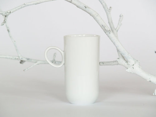White delicate tall porcelain cup for left handed person designed by Natalia Gruszecka for Endesign.