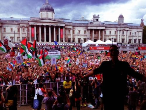Palestine upstages Israel at World Pride…again! July 11, 2012 Over the last few years, the Israeli government has been running a marketing campaign, 'Brand Israel', with a particular eye on gay tourism. Although there is a financial incentive in attracting the 'pink pound' to Israel, the key element has been to present an alternative image of Israel . At London's biggest outdoor party for the gay community on Saturday 7 July, this alternative image was described in Tel Aviv's promotional literature as 'fun, free, fabulous'.    World Pride, with a march through London and a rally in Trafalgar Square,  provided an ideal target audience for an initiative to 'pinkwash' Israel. Surely the fun-loving crowd would be receptive to the idea of partying on the beach in Tel Aviv – particularly with two gay Israeli acts on the main stage in Trafalgar Square? But as Harel Skaat, Israel's 2010 Eurovision entrant, came on stage,  a sea of  Palestinian flags sprang up in the audience and were waved high above the crowds  throughout his performance and through some excruciatingly bad lip-syncing from the next act, 4 Drag Queens from Tel Aviv. The Palestinian theme continued to snowball. The photo that World Pride host and television presenter, Gok Wan, tweeted from the stage to his 990,000 followers   showed Palestinian flags and the Palestine Solidarity Campaign banner  waving  prominently in the crowd. The photo went on to be retweeted at least 470 times. And just as the Tel Aviv promoters must have thought it couldn't get any worse, the veterans of London's first Pride march, 40 years ago, came onto the stage – carrying a Palestinian flag  and with one wearing a Free Palestine t-shirt!  The money Israel must have spent on trying to promote a tolerant image of itself was undone in moments by a few simple acts of solidarity with Palestine. There's a very clear lesson here for the Israeli government and the Hasbara unit: you can't spin your way out of criminal activity, and you can't cover up your occupation by uncovering the muscles of pretty gay men on a sunny beach in Tel Aviv. Source