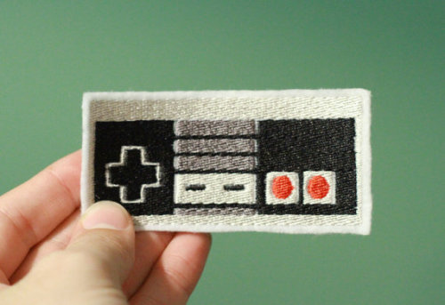 "Embroidered Iron-on NES Patch From OKSmalls: Buy now for $5.00 USD! Type in ""NINTENDARD"" in the coupon section during checkout to receive a 10% discount! This applies for all their items! Remember when gaming was about stomping goombas and saving the princess? The Nintendo patch will instantly transport you to a time when your favorite music was 8-bit themes from Mario, Zelda, or Tetris.Give this patch to your kid and watch them jump to the top of the flagpole and slide down as fireworks explode in the distance!The iron-on adhesive backing makes this patch a great addition to a backpack, shirt, hat, or anything you can imagine!"