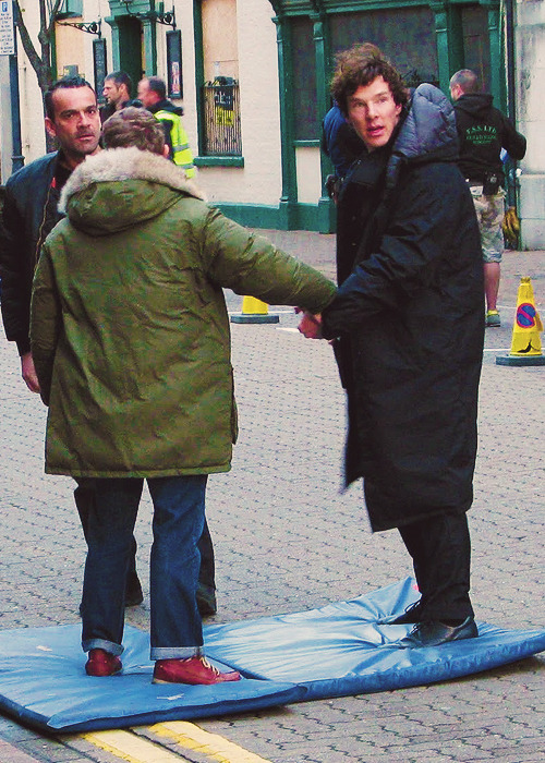 perfectbenny:   47/50 photos on set of Sherlock BBC series 2 [●]  Okay, kids. Time for some logic. Even if this is the scene where they are handcuffed (and I'm not sure it is), let's consider the jackets they are wearing. Clearly not in the actual shots, right? So they would have to take the handcuffs off for those jackets to go on and come off again. So why would they handcuff them with the jackets on? Possible conclusion A: Everyone on the god damn show ships Johnlock. Possible conclusion B: They are not currently handcuffed, and they just hold hands like bros. Possible conclusion C: All of the above. Side note: Martin/John, wtf are those shoes.